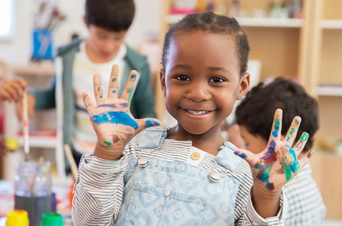 Young smiling child with painted hands in a classroom.